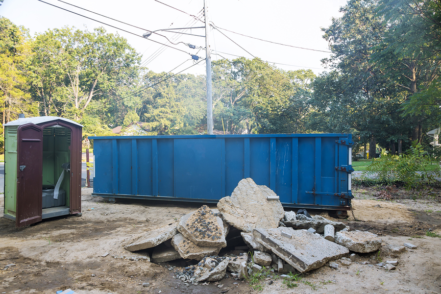 removal of debris construction waste building demolition with rock and concrete rubble on portable bio toilet cabins at the construction site